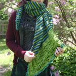 long triangular striped shawl with deep lace border on one edge and crochet picot edge
